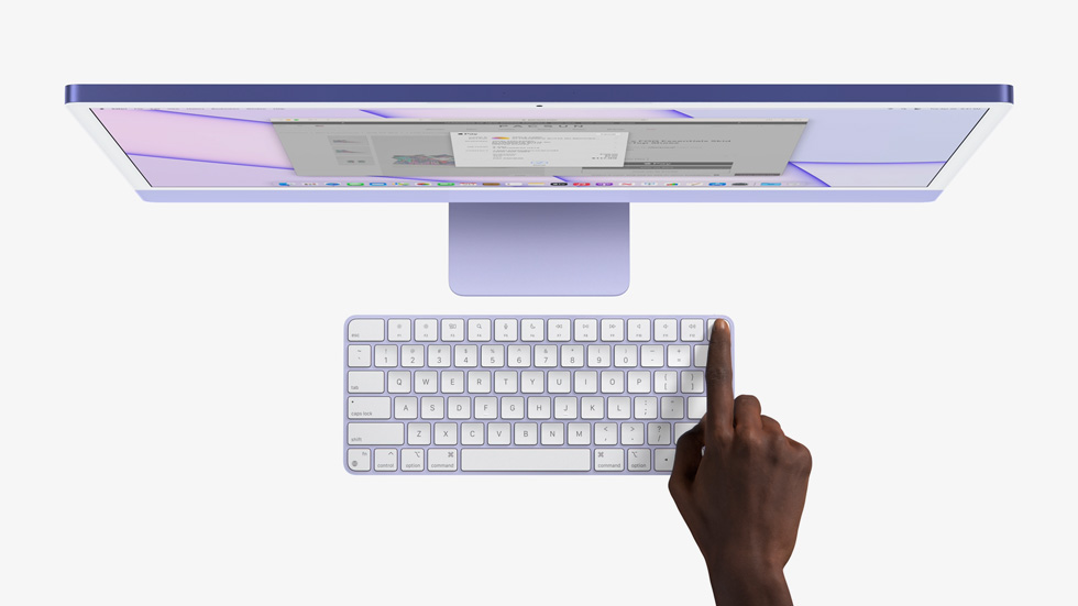 A finger presses Touch ID on Magic Keyboard to turn on iMac.