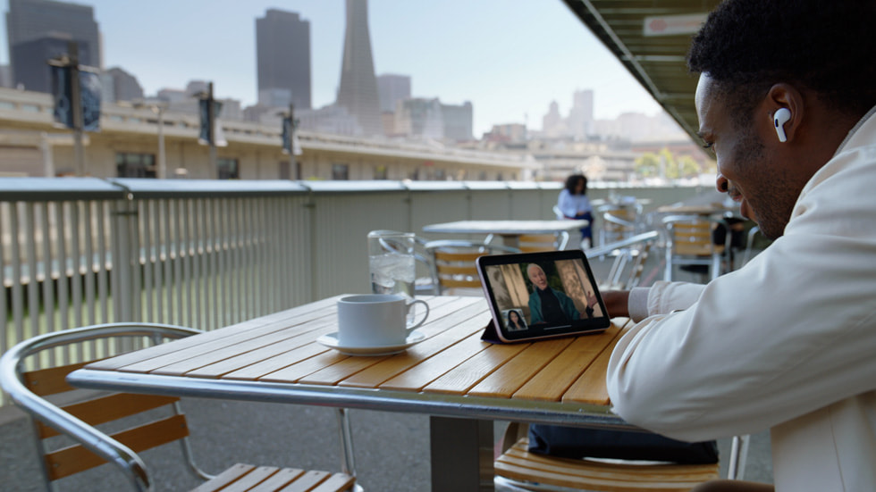 A person having coffee outside while using FaceTime and AirPods Pro with iPad mini.