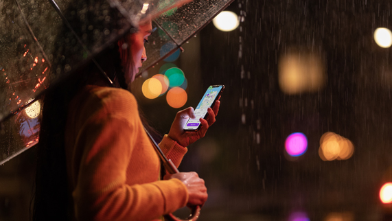 Woman holding an umbrella and iPhone Xs in the rain.