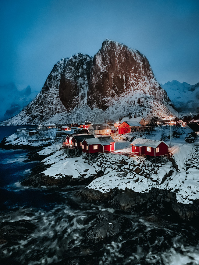 Small village of red cabins next to the sea, with a snowy mountain behind them.
