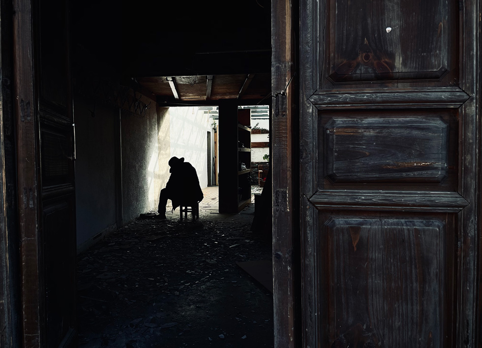 Beyond an opened door, a figure sits amid debris and shadows.