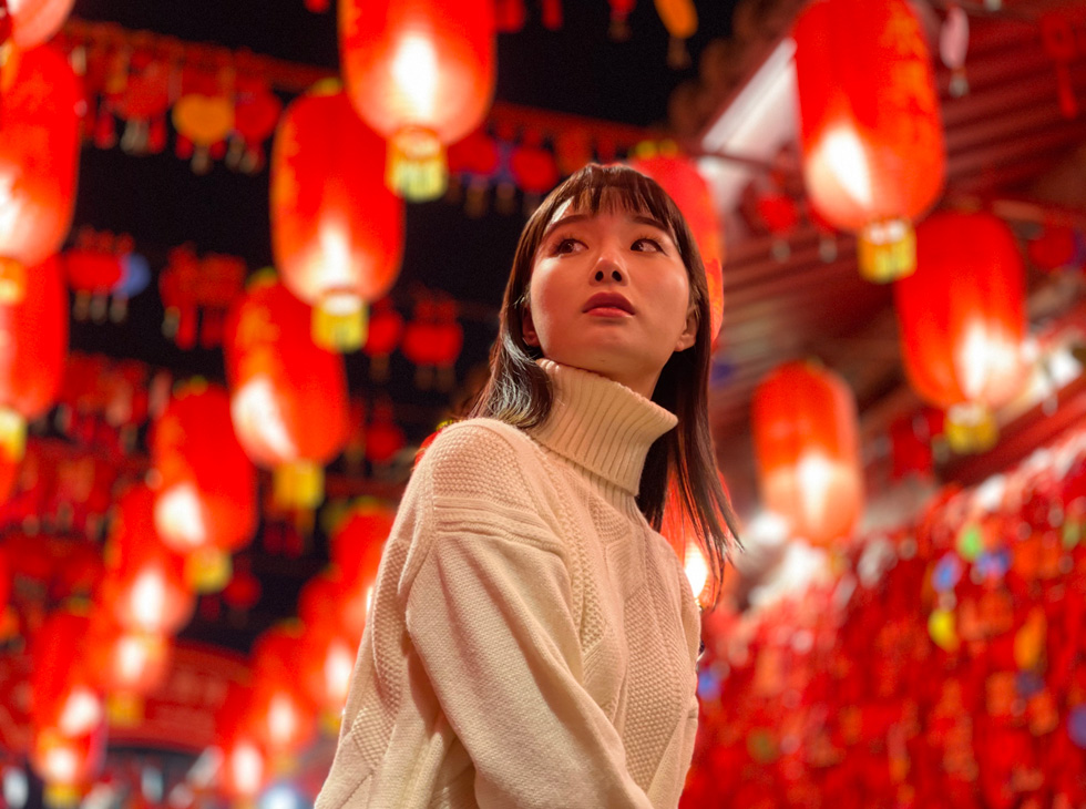 A woman photographed among glowing red paper lanterns strung overhead.