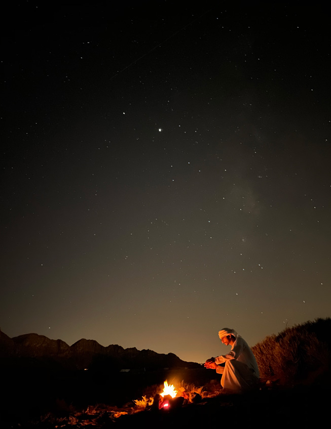 A night shot of a man sitting in front of a campfire in the desert.