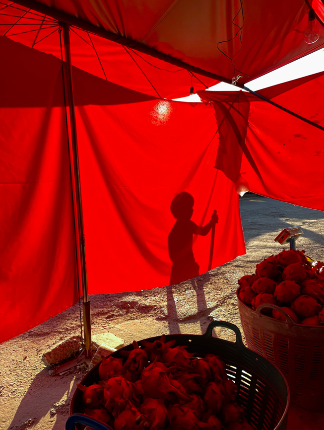 A red tarp tasked to block out the sun sets off a shadow of a child playing.