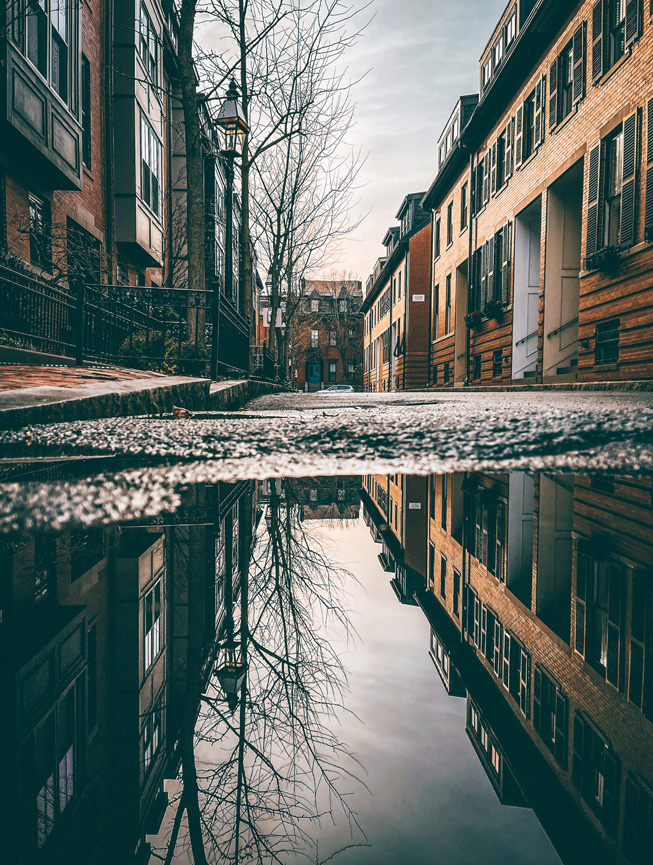 A large puddle of water on the street reflects its surroundings and the sky above.