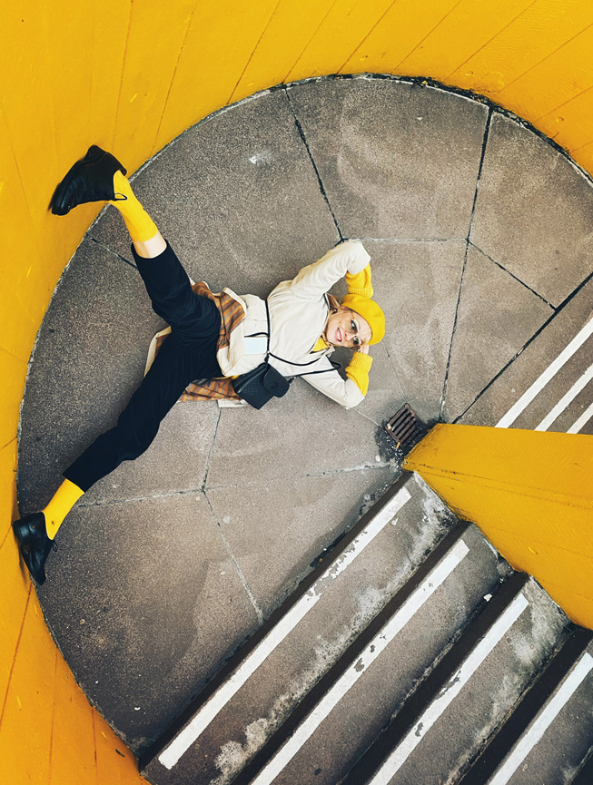 A person poses on the landing of a yellow-walled stairwell.