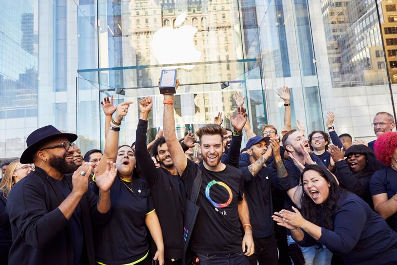 Teammitglieder von Apple mit iPhone 11 Pro-Kunden außerhalb vom Apple Fifth Avenue.