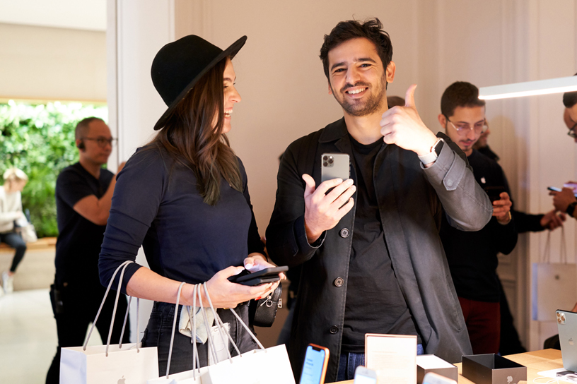 Ein Teammitglied von Apple hilft einem Kunden, der ein iPhone 11 Pro im Apple Champs-Élysées in der Hand hält.