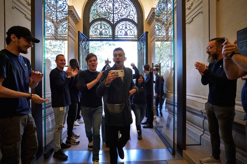 Apple team members greet customers entering Apple Champs-Élysées.