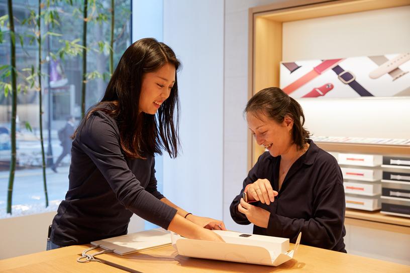 Ein Teammitglied von Apple hilft einer Kundin, die Apple Watch Series 5 im Apple Marunouchi auszuprobieren.