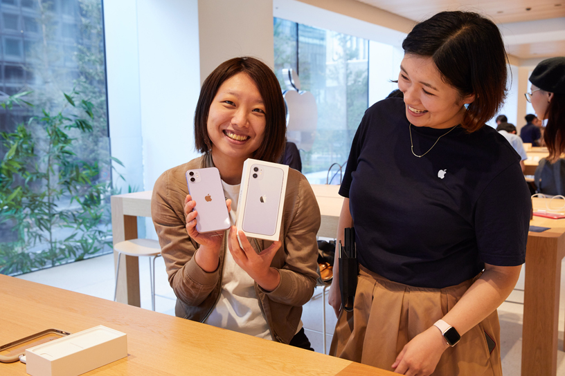 Customer holding up iPhone 11 and box next to an Apple team member at Apple Marunouchi.