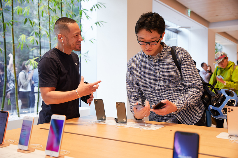 An Apple team member talks to a customer checking out iPhone 11 Pro at Apple Marunouchi.