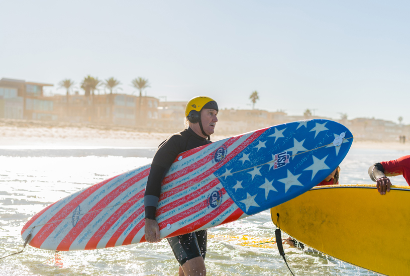 Leason heads out into the water with his custom Hank Warner competition surfboard.