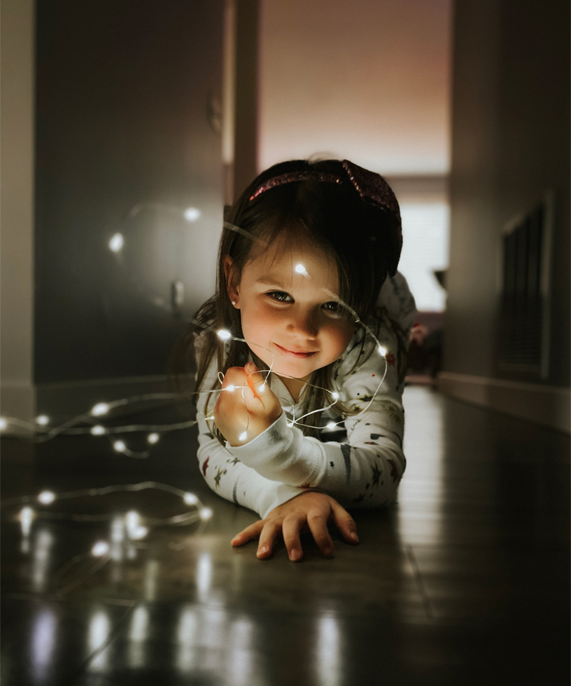 A portrait of a young girl playing with string lights.