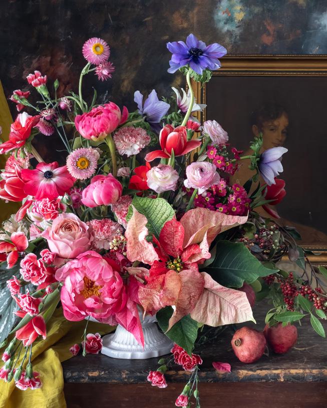 Arreglo floral frente a un cuadro enmarcado.