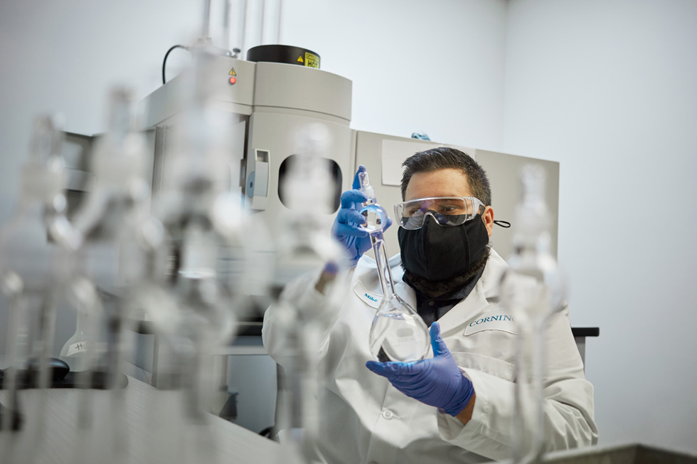 A Corning technician, outfitted in goggles, mask, and gloves, handles glass beakers.