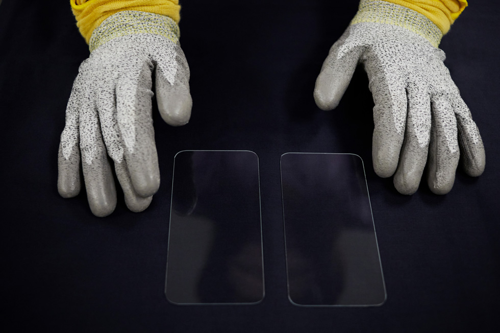 Gloved hands display new front covers for the iPhone 12 lineup.