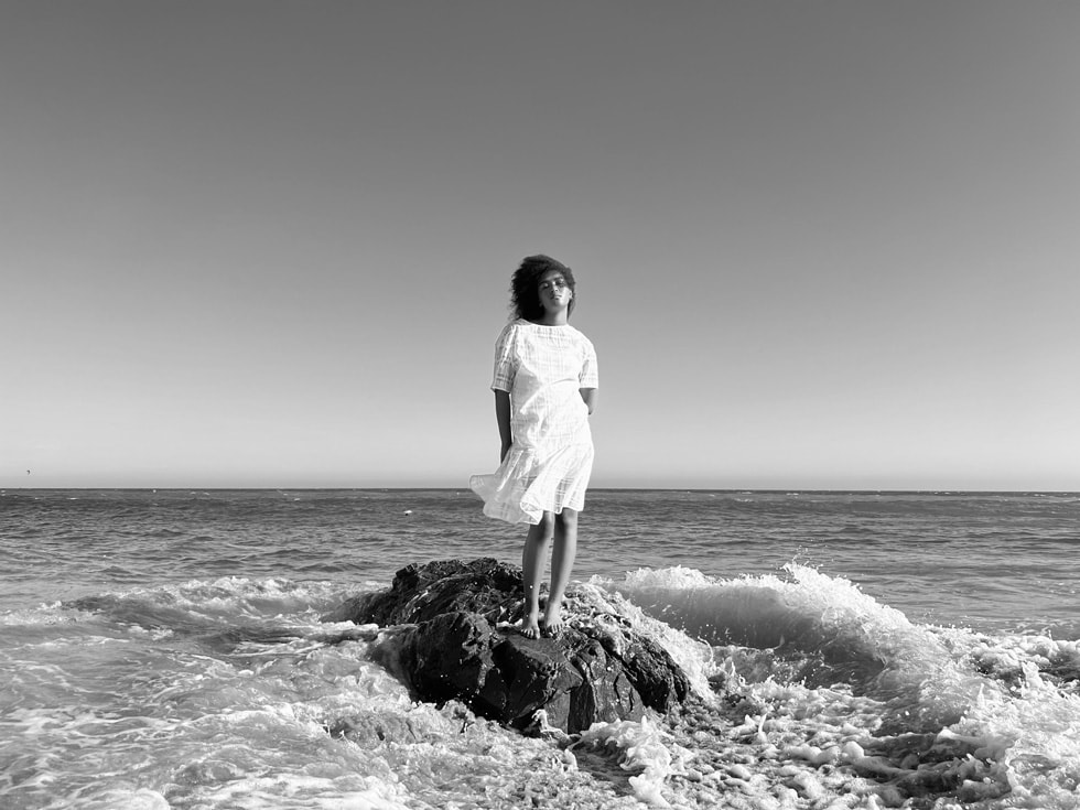 Woman standing by the ocean taken on iPhone 13 Pro's Wide camera with sensor-shift OIS.
