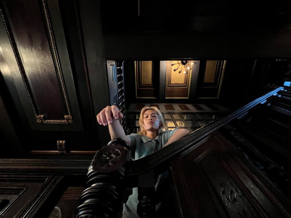 Porträtt av en man i en mörk trappa taget med ultravidvinkelkameran på iPhone 13.