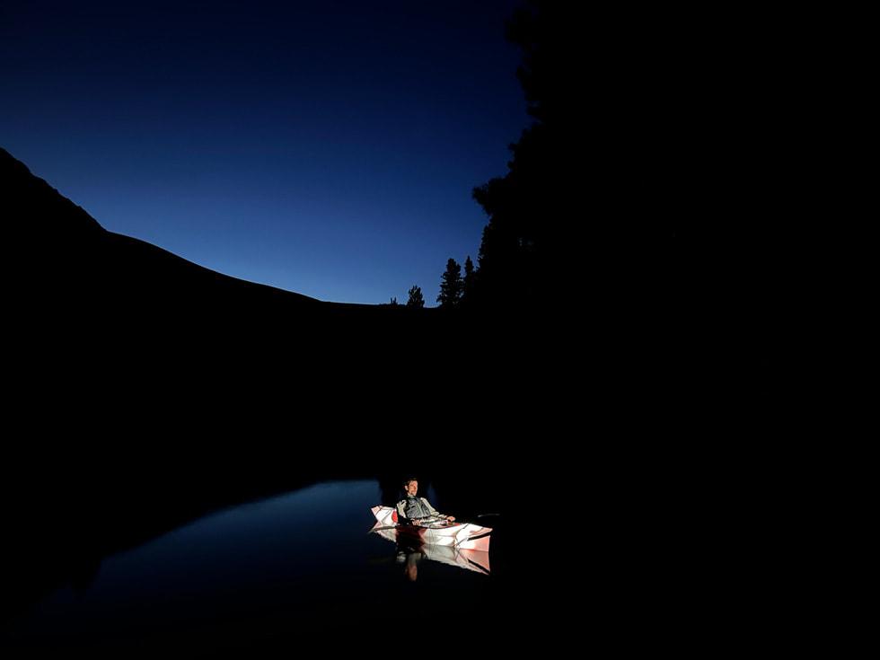 Foto nocturna de un hombre en una canoa hecha con el gran angular del iPhone13 en modo Noche.