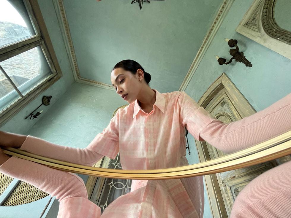 Bild i spegelperspektiv av en kvinna tagen med ultravidvinkelkameran på iPhone 13.