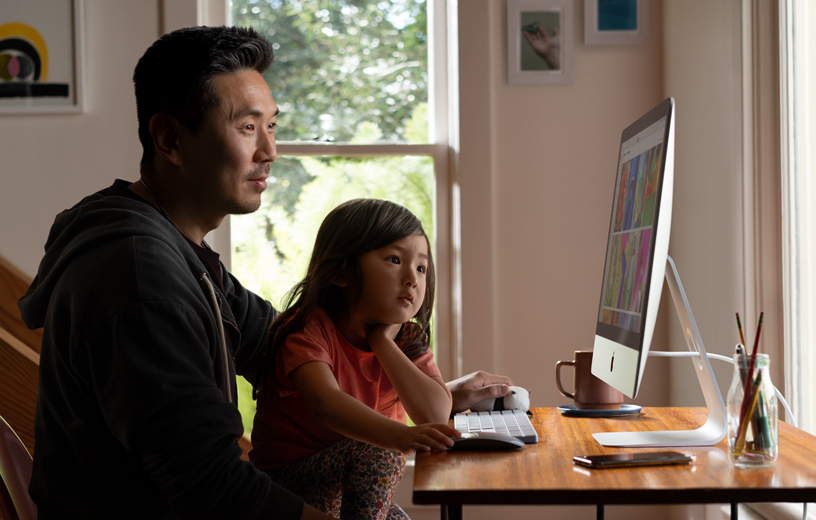 A father and daughter look at pictures on an iMac in their home.