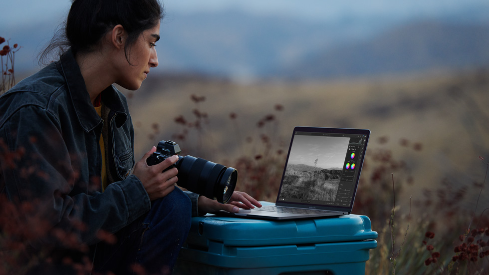 A photographer using her camera and M1-powered MacBook Air.