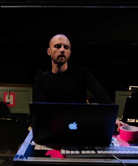 Enrico de Trizio standing behind a MacBook Pro.