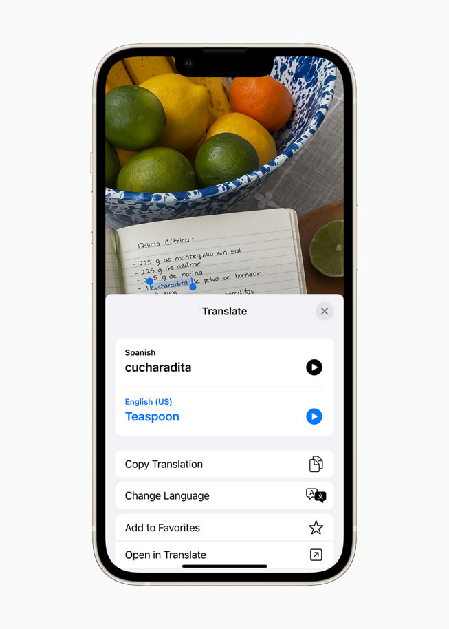 iOS 15 using Translate to translate Spanish text to English on a starlight iPhone 13.