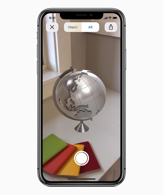 iPhone X showing an AR globe on a desk.