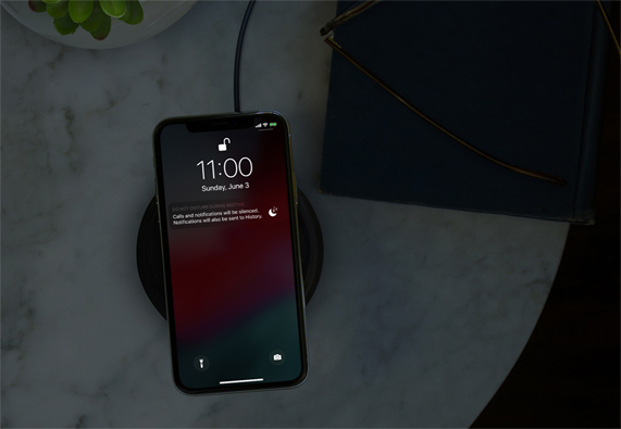 iPhone in a dark room on a wireless charger showing Do Not Disturb.