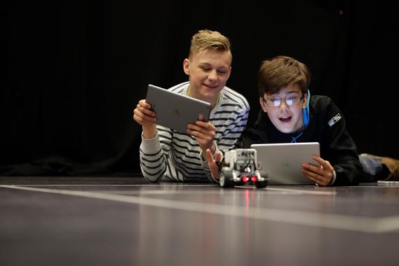 Zwei junge Leute steuern ein Roboterauto mit iPads.