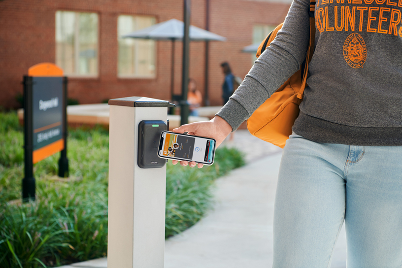 A student uses a contactless student ID on iPhone to enter a campus building.