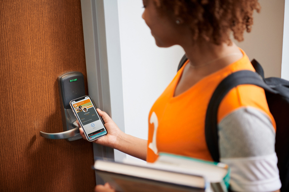 A student uses their ID on iPhone to enter a room.