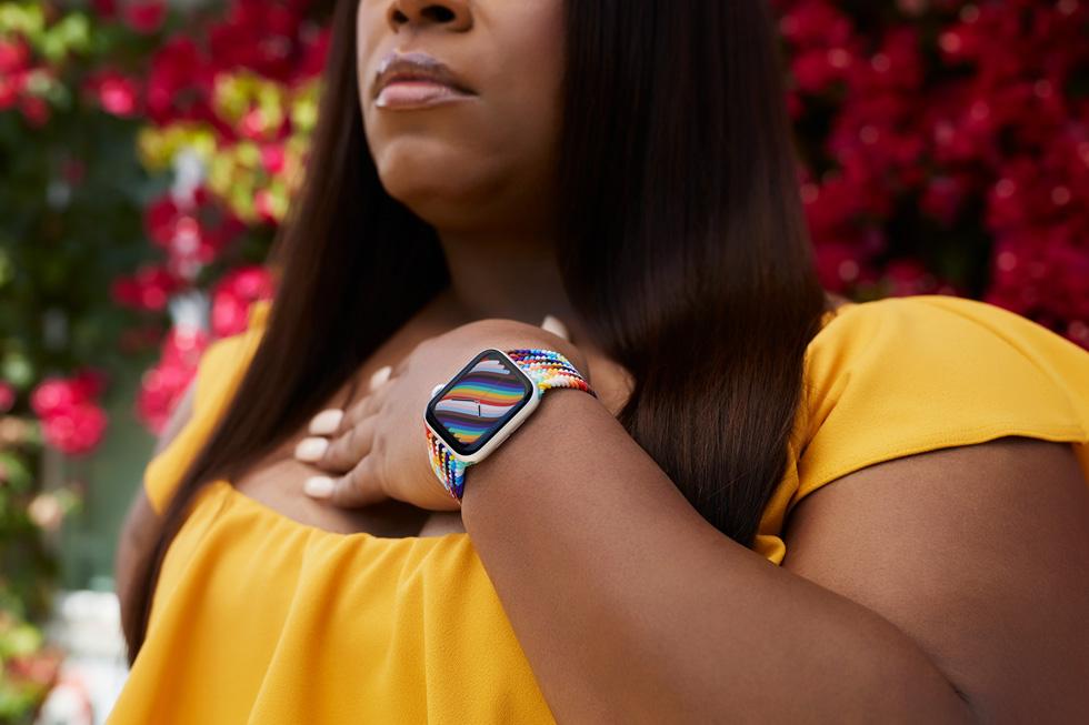 Apple Watch 프라이드 에디션 브레이드 스포츠 루프와 시계 페이스를 착용하고 있는 LGBTQ+ 지지자 도미니크 모건의 클로즈업 사진.