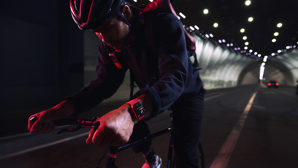 A cyclist wearing AppleWatchSeries7 rides through a tunnel at nighttime.
