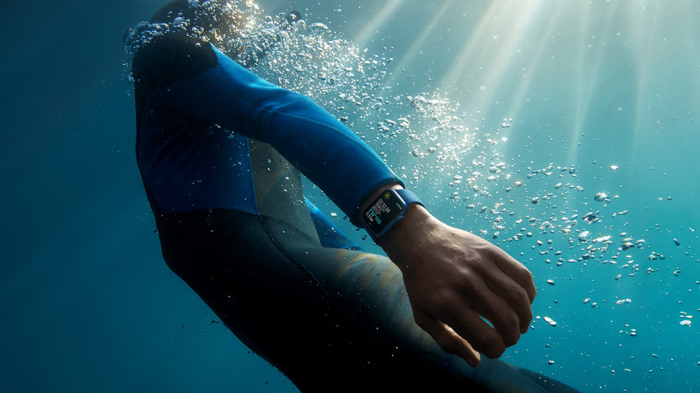 A surfer looks at Apple Watch Series 7 on their wrist in the ocean.