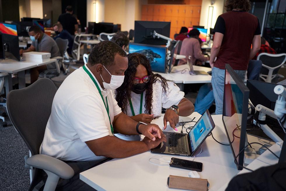 Un profesor enseña a un compañero en una MacBook en la Apple Developer Academy en Detroit.