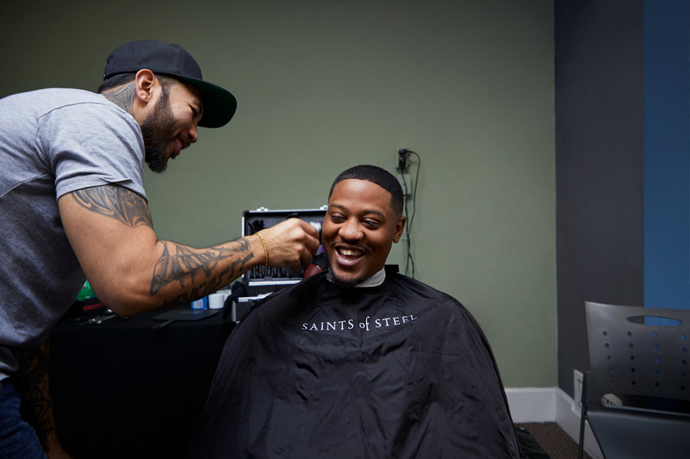 A barber giving a young man a haircut.