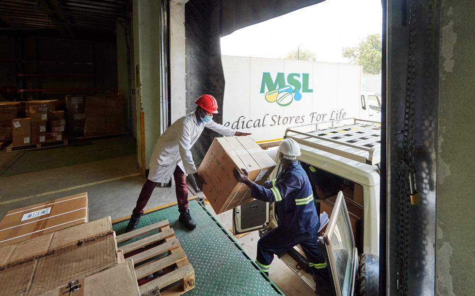 Workers in Zambia at a warehouse loading a box into a vehicle