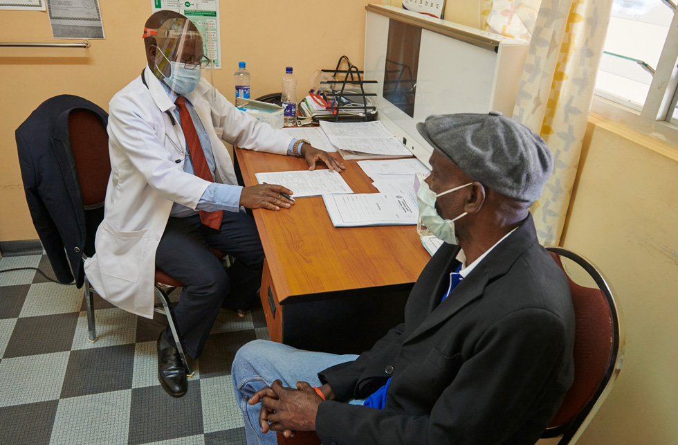 Hospital clinician Samson Tembo interviewing patient Wilson Kalunga in Zambia.