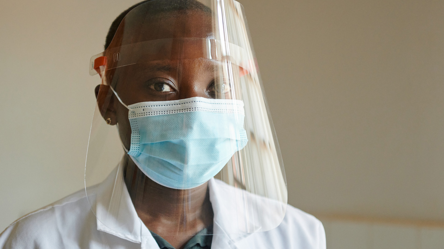 A healthcare worker in Zambia wearing a face shield and mask.