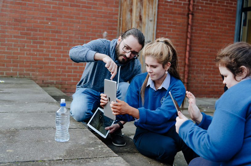 A young woman uses iPad to shoot a photo, with help from an Apple volunteer.
