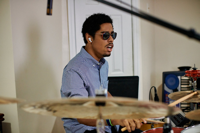 Mathew Whitaker plays the drums at his home.