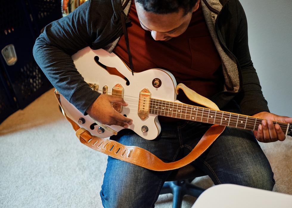 Rhys Richard practices guitar.