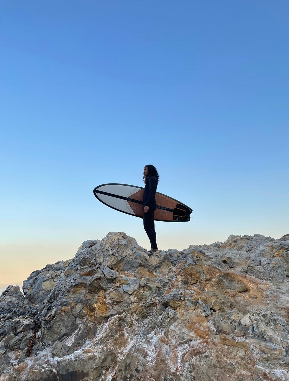 Marikah mit Surfbrett, stehend auf einem Felsvorsprung.