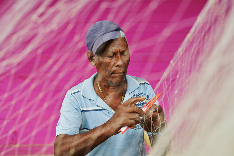 A fisherman in San Antero hand-weaves a fishing net.