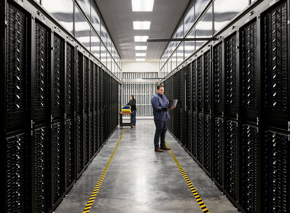 Two employees in a server room of an Apple data center.