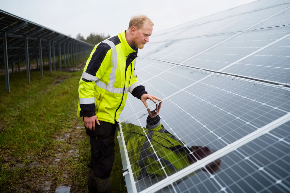 A worker examines a solar array.