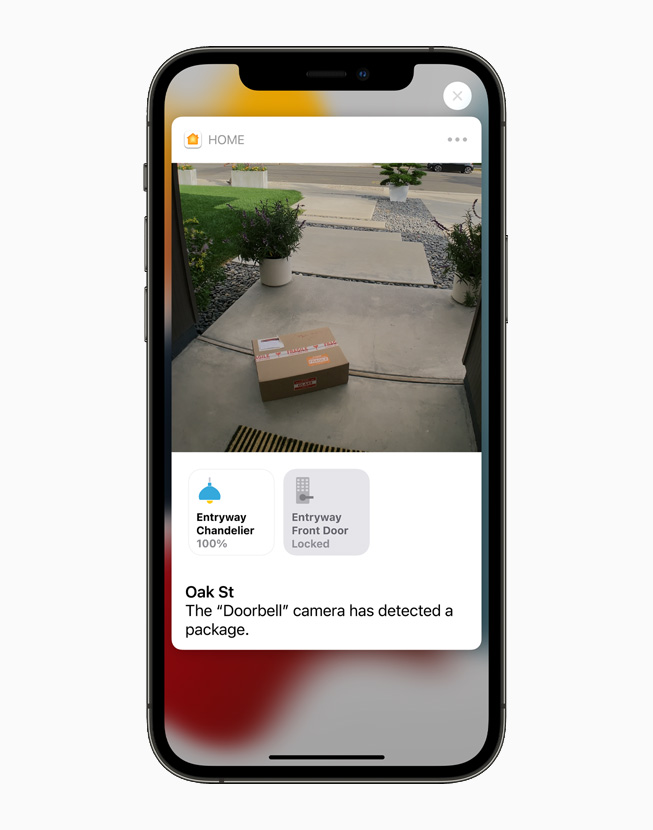A HomeKit-enabled camera shows a package left near the front door, displayed on iPhone 12 Pro.